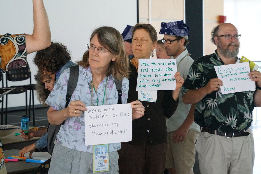 Sylvia Holmes, Paula Holden, and Raines Cohen propose Open Space sessions on the League of Cities, addressing activists' needs, and eco-villages, respectively. Photo by Teresa Konechne.