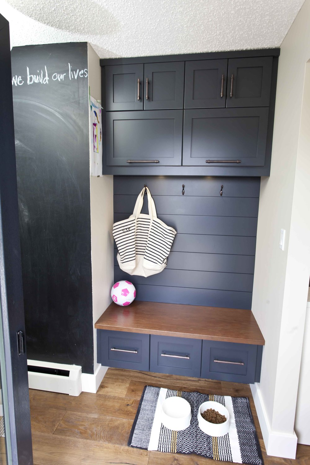 The back entry nook is converted into a functional storage space and feeding station for the dog.