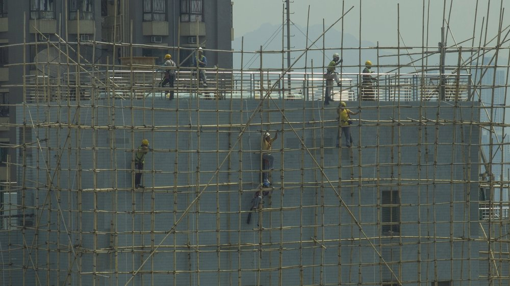 In Hong Kong, construction workers called taap paang begin to dismantle the bamboo scaffolding that earns them their name. The use of bamboo for scaffolding has increased in recent decades as the material has become increasingly cheaper than steel or other metals. (Kaylee Tornay)
