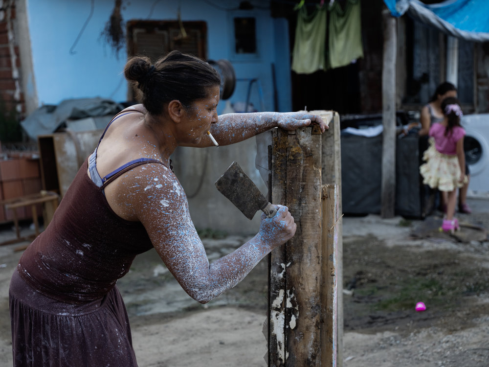"Gilbana,  mother of five, is the furnace of this ""tribe"". She works tirelessly  from dawn to dusk. At times she leaves the family for months for  better-paid season work. Here she chops down an old wooden window frame  to start a fire in their stove."