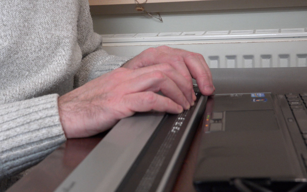 A blind musician reading music from a Braille terminal.
