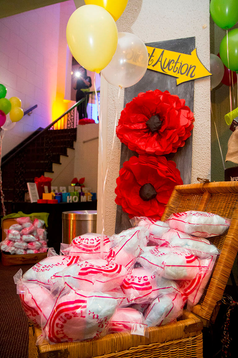 Large basket filled with packaged cotton candy for guests, with paper poppy flower decoration behind - Historia Wedding and Event Planning
