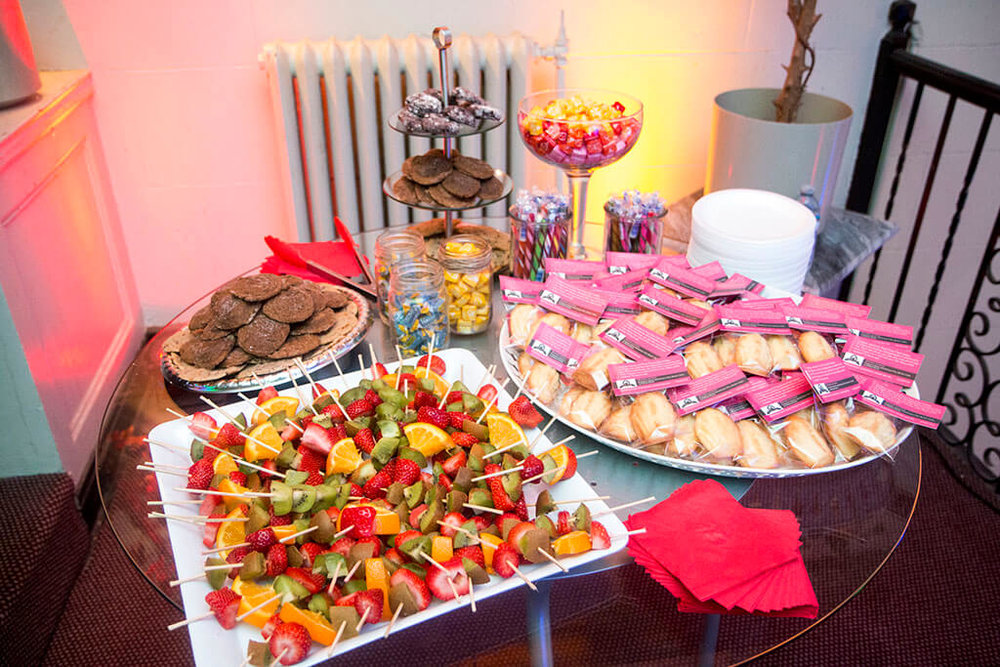 Dessert/sweets table with various treats, including fruit skewers, Madeleines, cookies and candy - Historia Wedding and Event Planning