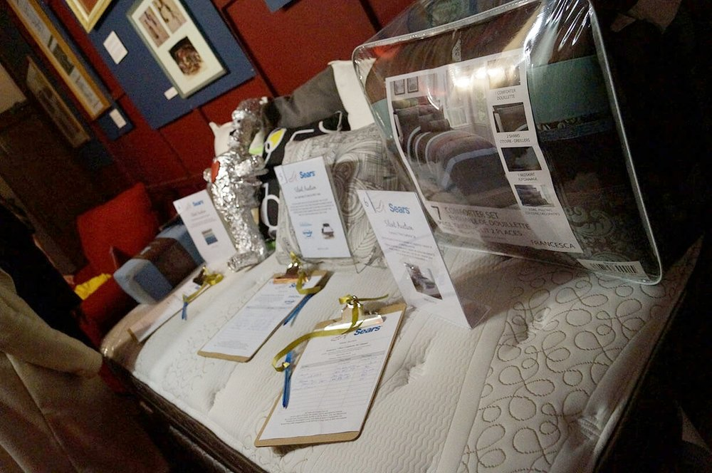 Sponsored event mattress from Sears with display of other sponsored event raffle/silent auction items - Historia Wedding and Event Planning
