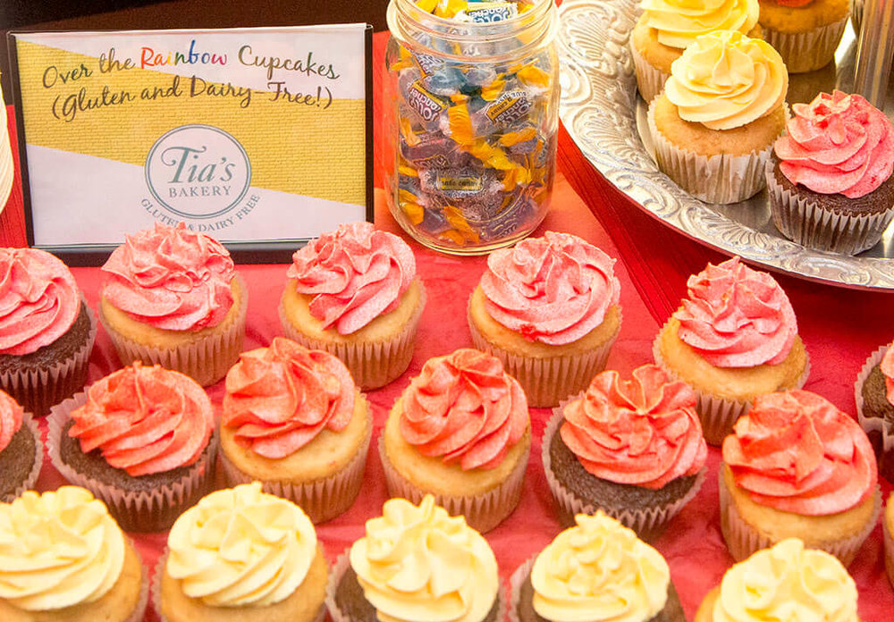 Closeup of rainbow cupcake display on dessert/sweets table with Tia's Bakery sign - Historia Wedding and Event Planning