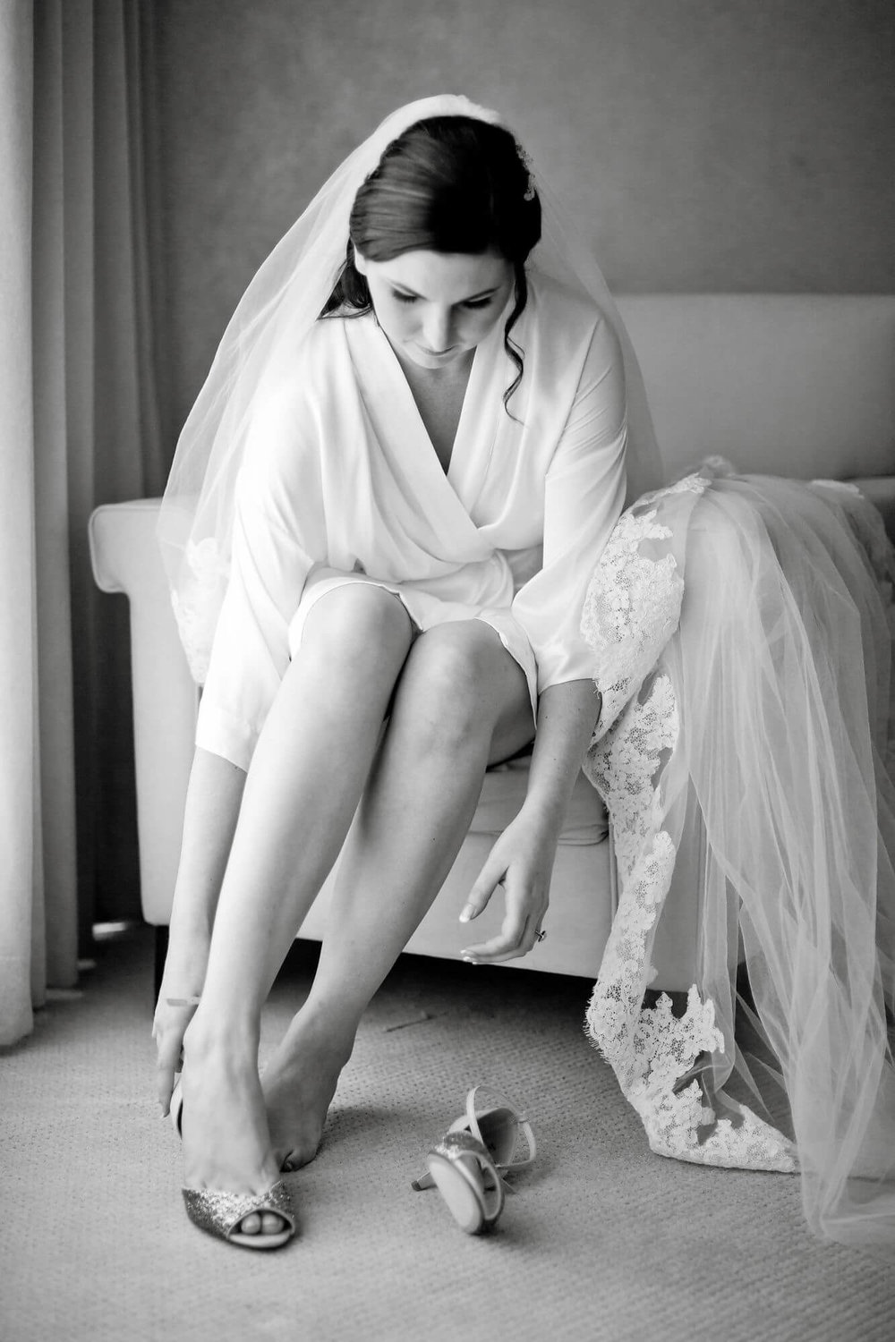 Black and white photo of bride sitting and getting ready in her hotel room, putting on shoes - Niagara wedding - Historia Wedding and Event Planning
