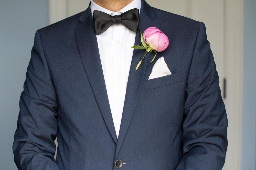 Photo of groom's torso in navy suit with pink peony boutonniere, black bowtie and white pocket square - Historia Wedding and Event Planning