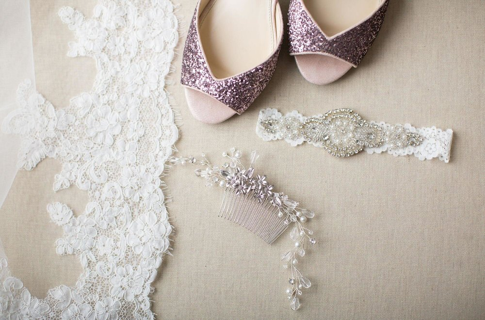 Artistic photo of wedding lace, white and silver jeweled garter, white and silver jeweled hair pin and glittery pink shoes - Niagara wedding - Historia Wedding and Event Planning