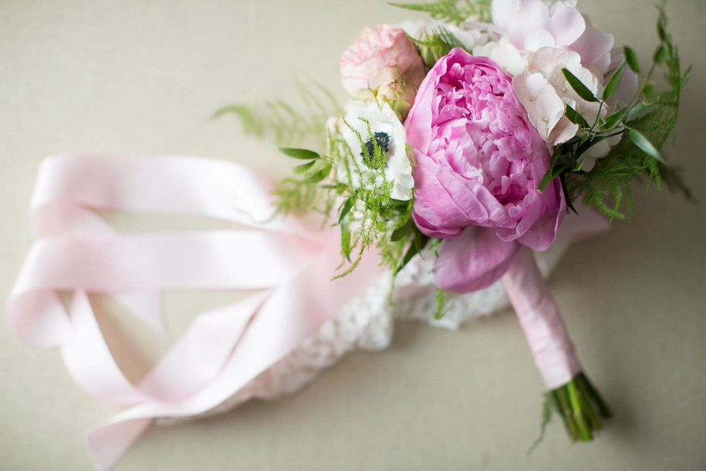 Artistic photo of petite white and blush bouquet with pink peony and pink ribbon - Niagara wedding - Historia Wedding and Event Planning