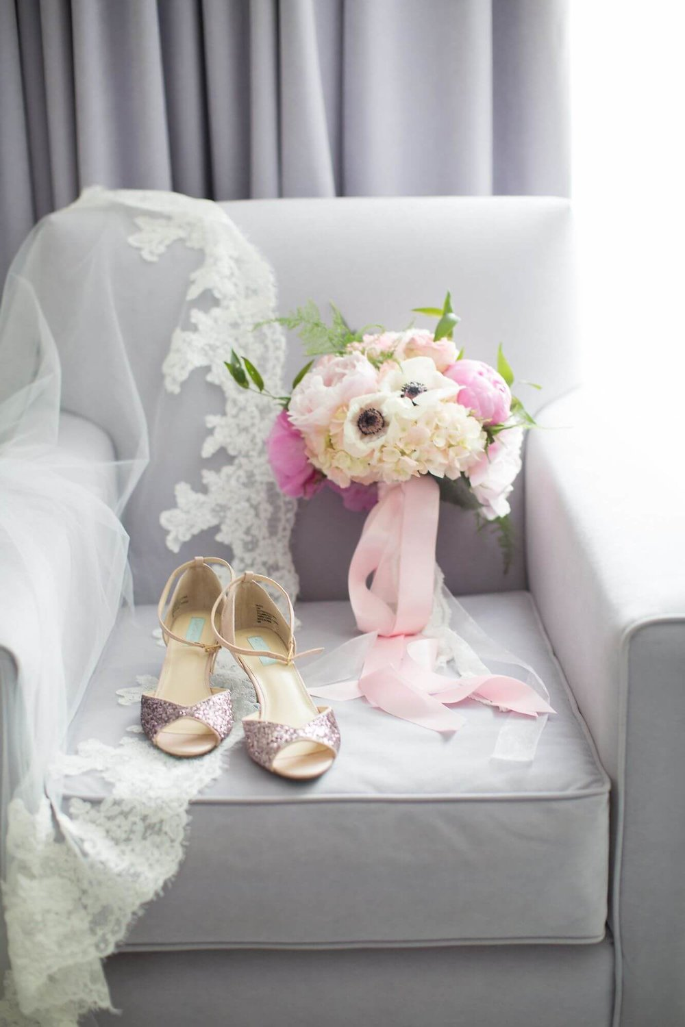 Artistic photo of bride's white and blush pink wedding bouquet on grey armchair with lacy veil and glittery pink heels - Niagara wedding - Historia Wedding and Event Planning