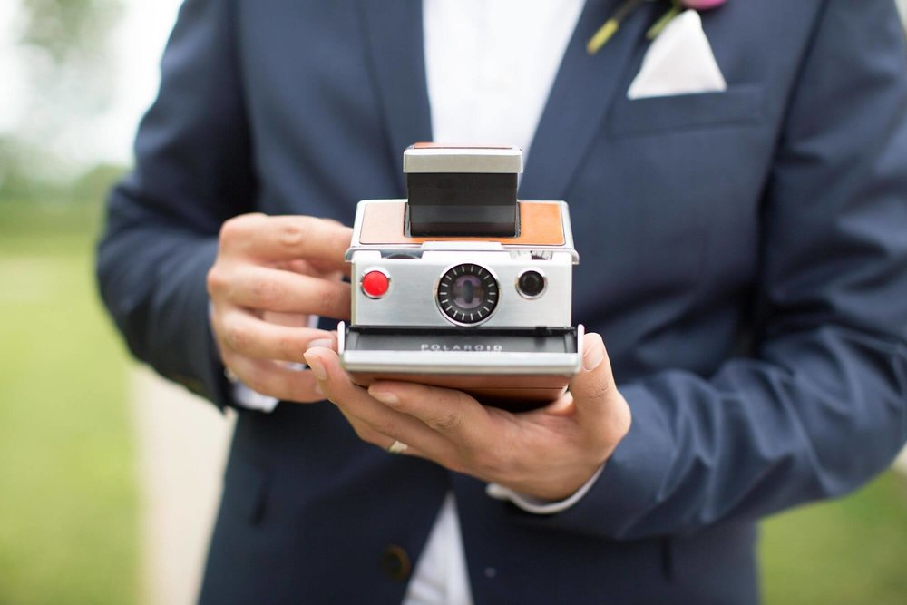 Photo of groom's torso with closeup of him holding a vintage polaroid camera - Niagara wedding - Historia Wedding and Event Planning