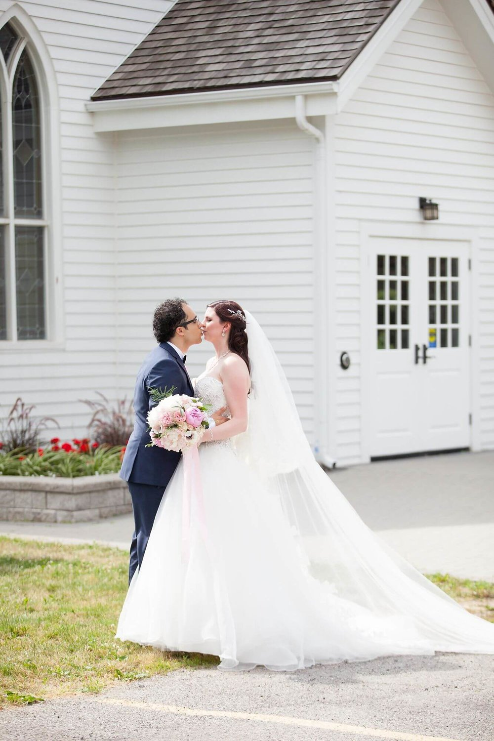 Bride and groom kissing after just being married, standing in front of Queenston chapel - Niagara wedding - Historia Wedding and Event Planning