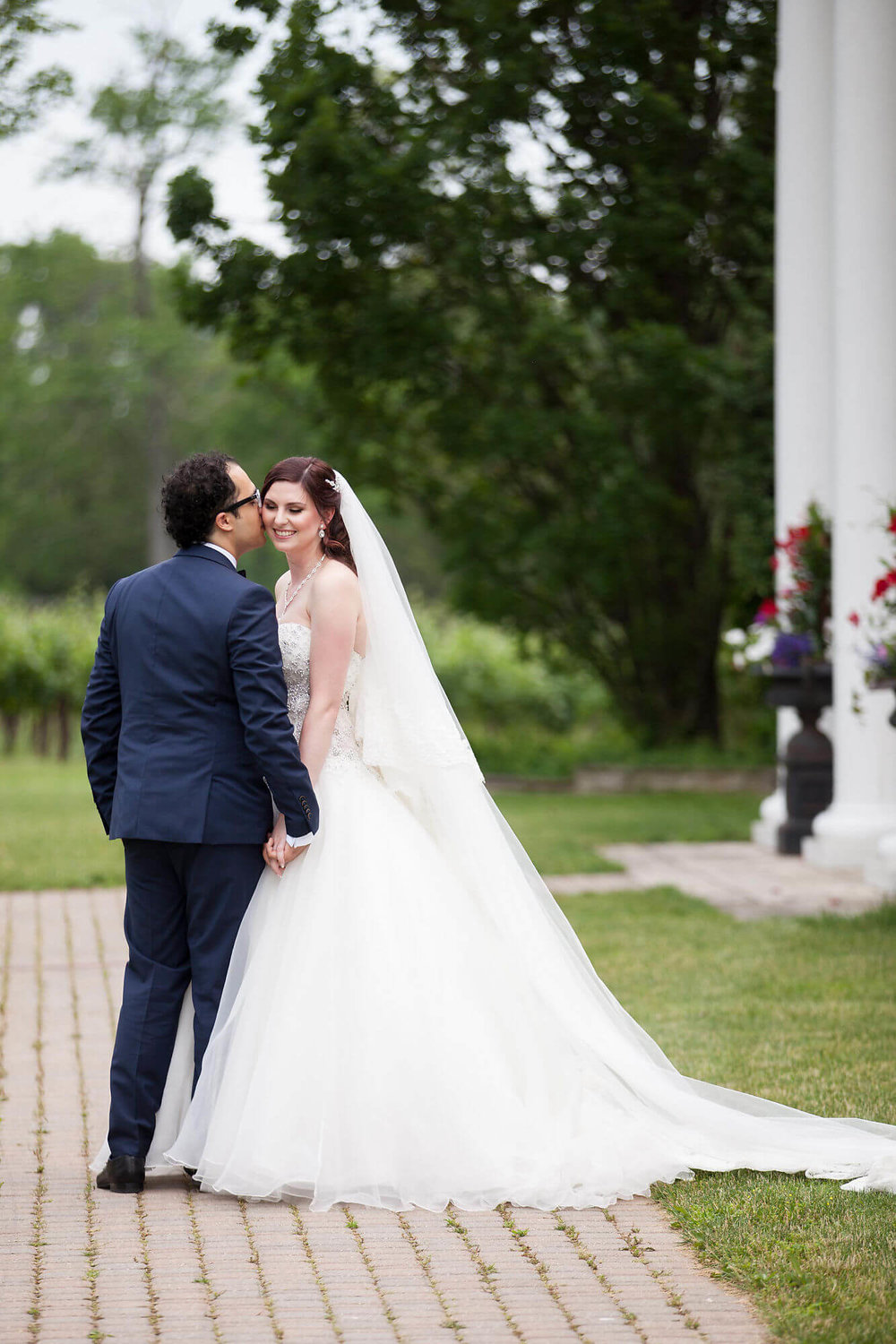Photo of just married wedding couple with groom kissing bride on the cheek - Historia Wedding and Event Planning