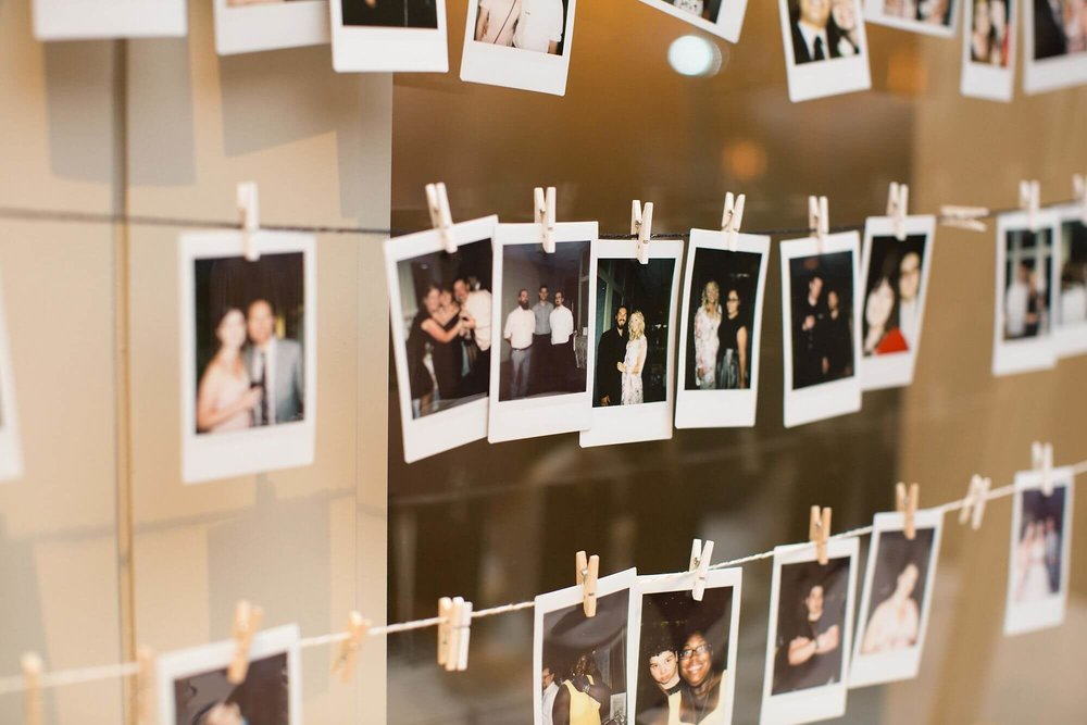 Artistic photo of hanging polaroid pictures on clothespins at wedding photo table - Niagara wedding - Historia Wedding and Event Planning