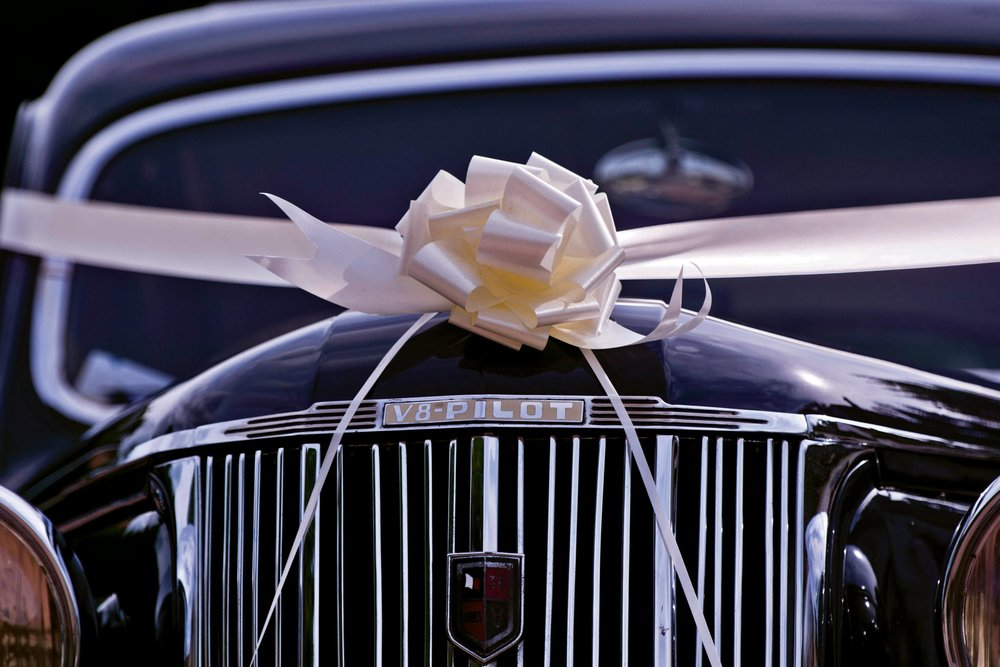 black wedding limousine with white ribbon and bow, ready to pick up wedding couple