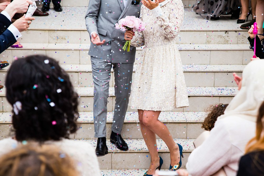 just married couple walking down stairs out of church with confetti