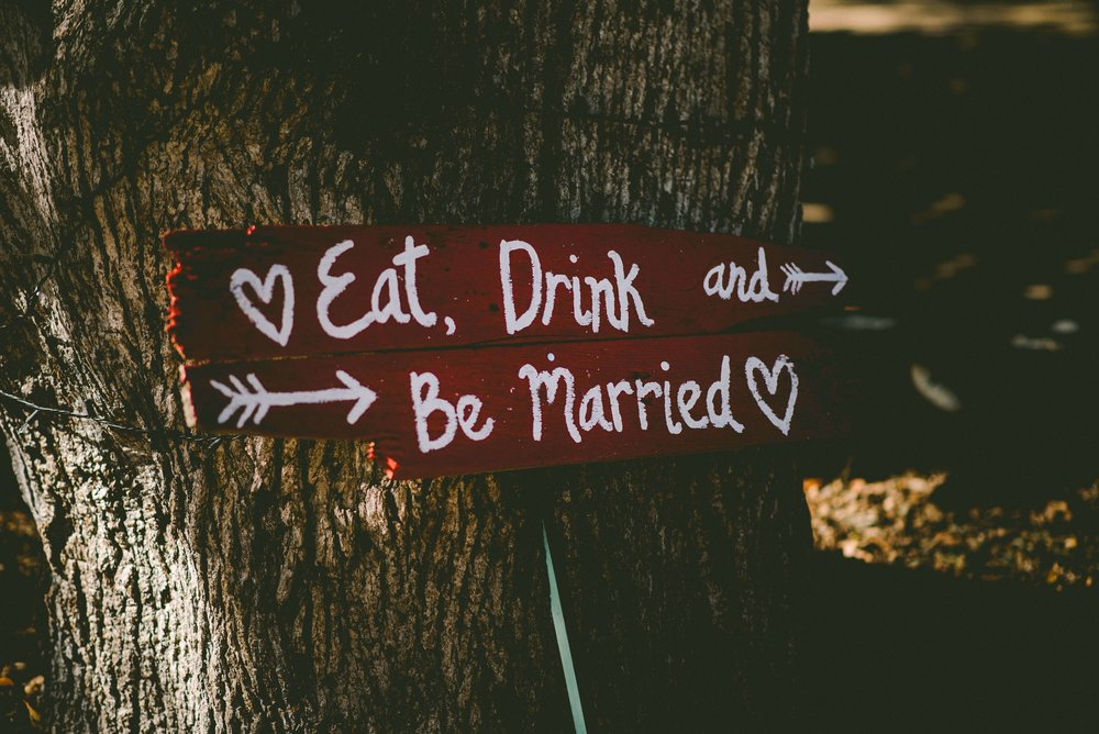 """Wedding signage leaning against a tree - """"Eat, Drink and Be Married"""""""
