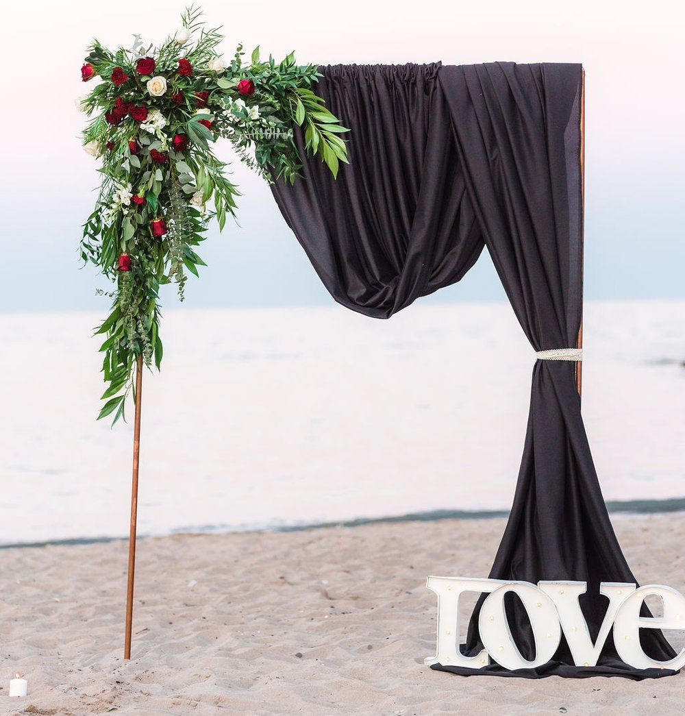 bold wedding archway with black drape, dramatic floral accents and love marquee