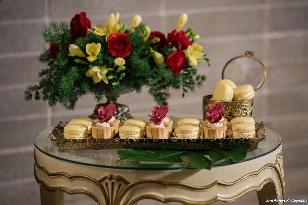 footer banner of beautifully decorated coconut tartlettes and vanilla macarons for sweet table display