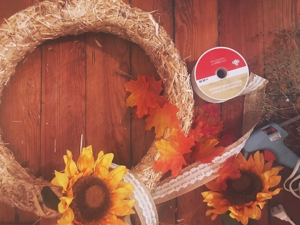 You will need: - 🎃 1 straw or grapevine wreath🎃 1-2 bundles of burlap ribbon- I found a ton of cute ribbon at Michaels🎃 1 bundle of faux sunflowers🎃 low temp hot glue gun and glue sticks🎃 any extra fall stuff you want to add- leaves, acorns, pine cones, dried baby's breath, etc.