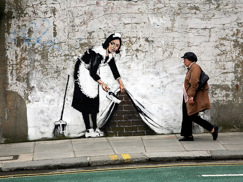 Banksy (2006) Sweeping it Under the Carpet. Stencil graffiti on a wall in London.
