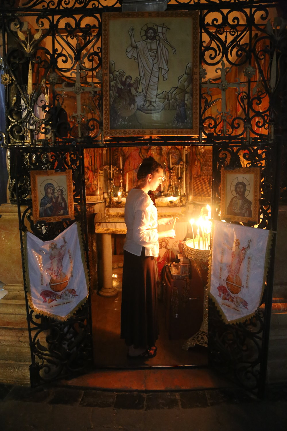 Lighting a candle in the tomb of Jesus Christ