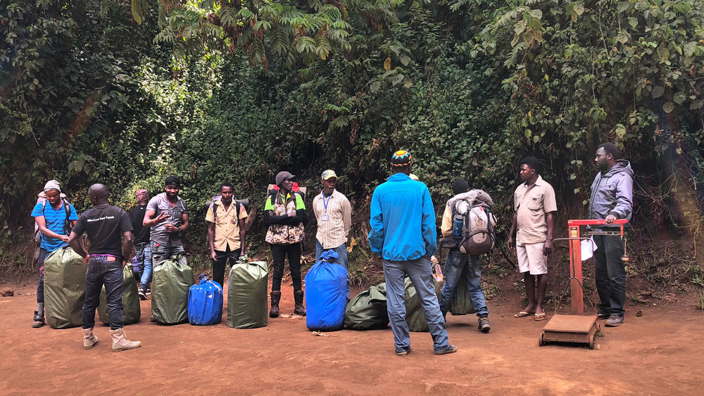 Our porters, lining up to get the gear weighed before starting the hike. Each porter may carry up to 32 lbs (15 kg).
