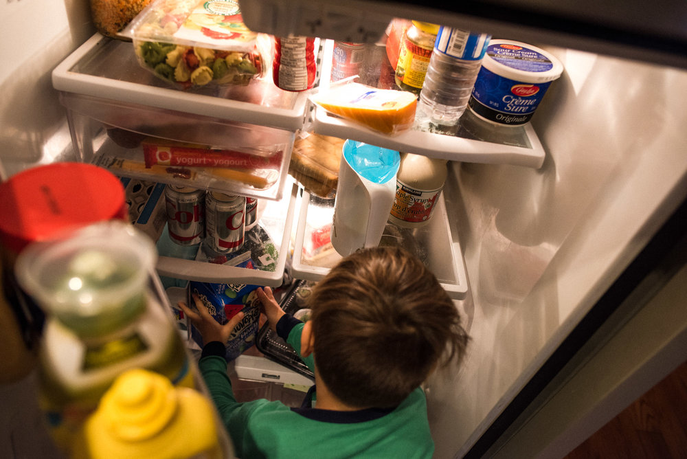 boy takes out juice carton from the fridge