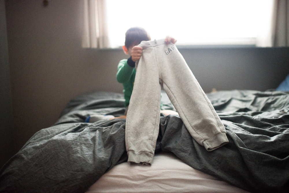 boy holds up pants