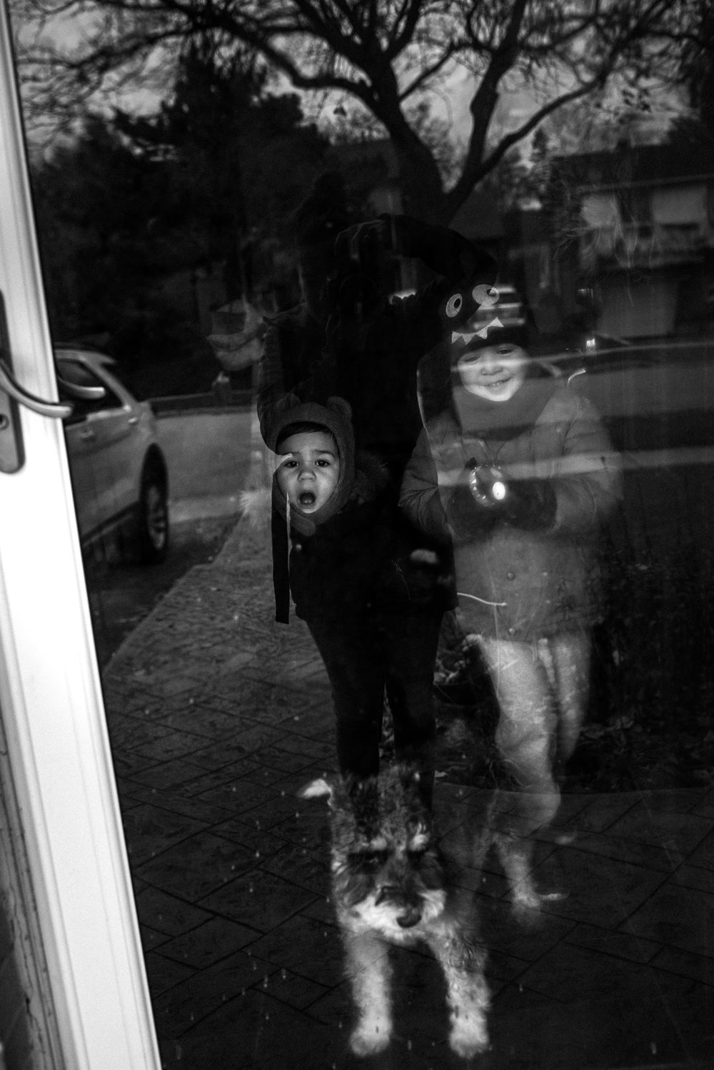 children's faces in black and white through the outside door