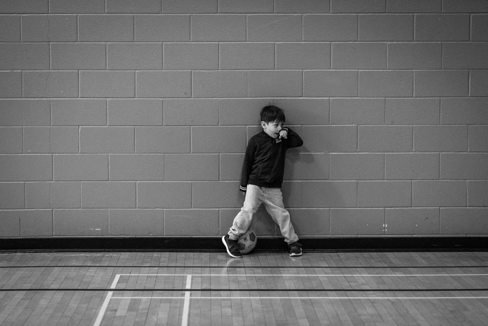 boy stands against gym wall at soccer practice