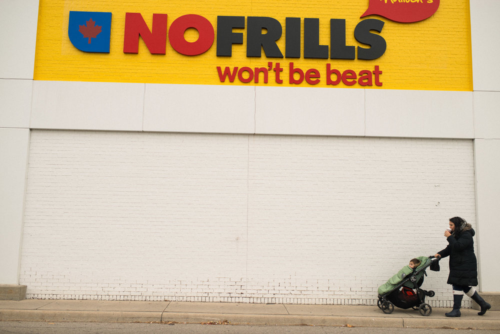 mom with coffee pushes stroller in front of no frills