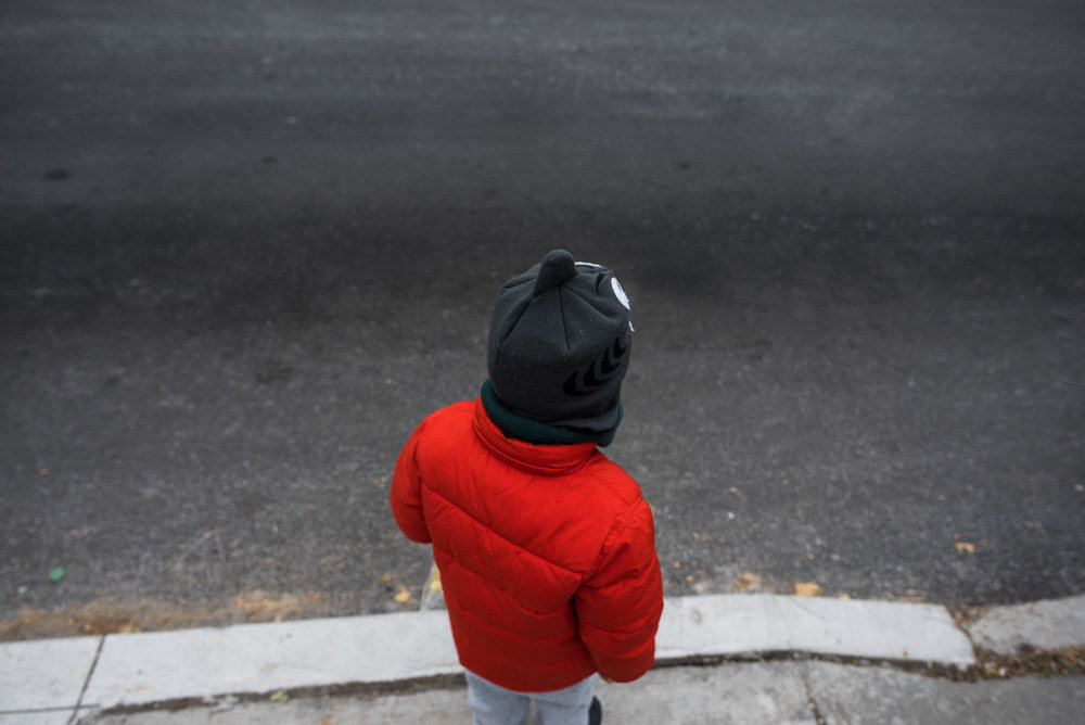 boy in orange coat stands at the curb