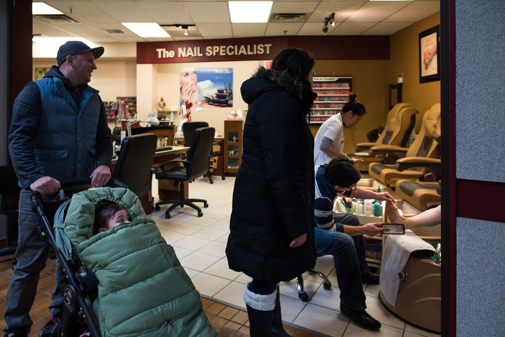 family with stroller talks to lady getting a pedicure at beauty salon