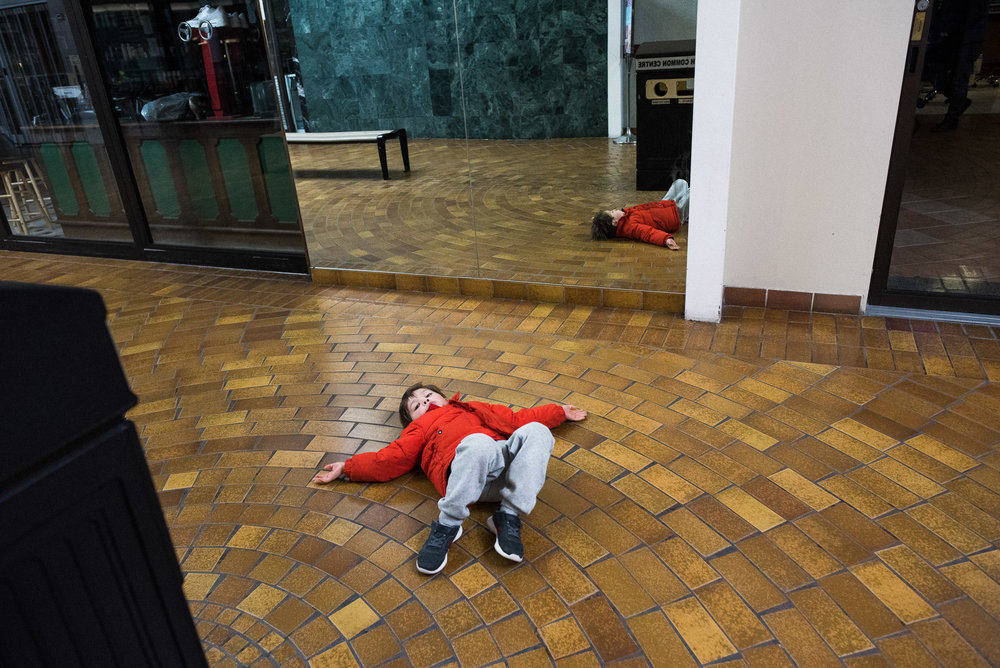 boy in orange coat lays on the floor of the mall