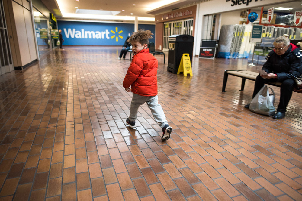 boy makes a silly face while walking through the mall