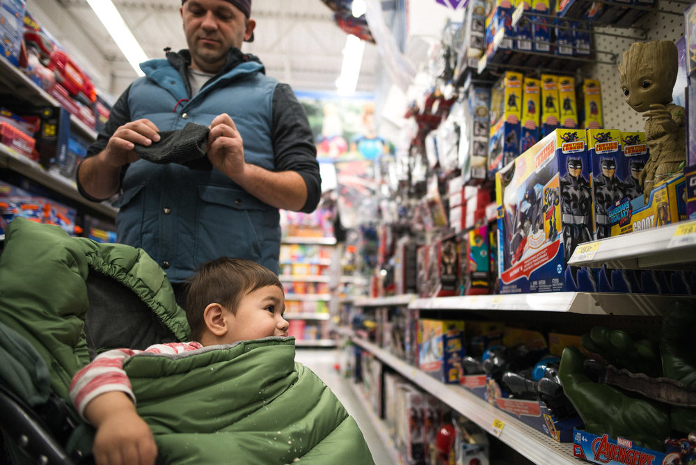 dad distracted while toddler in stroller looks at toys on the shelf