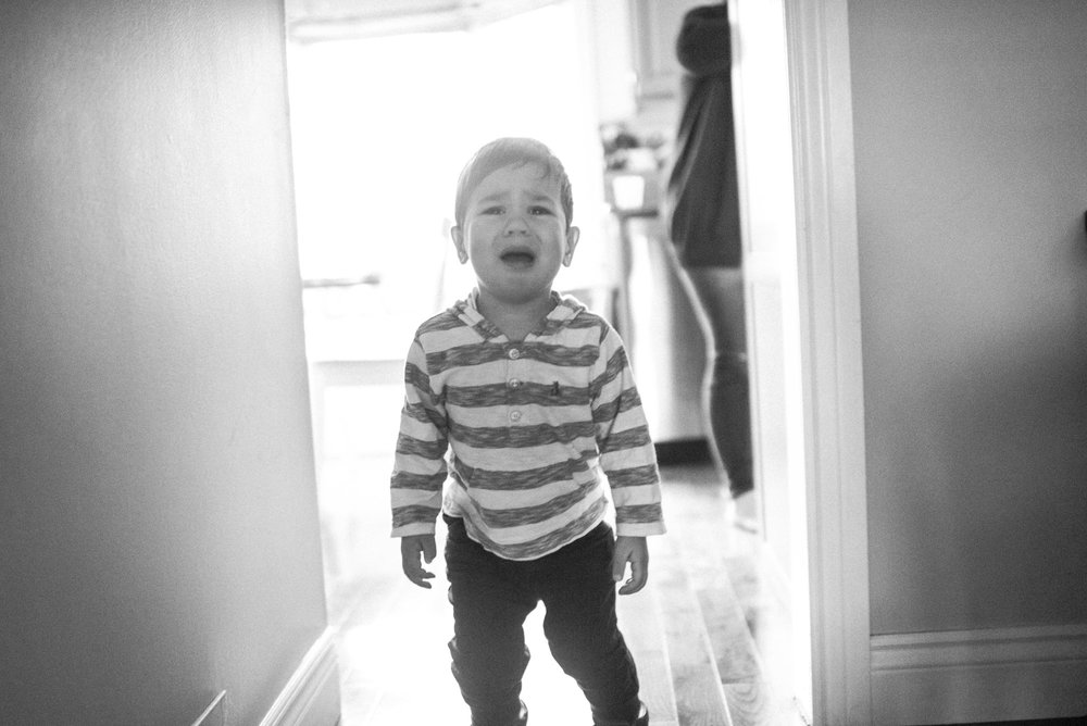 black and white photo backlit boy cries in the hallway