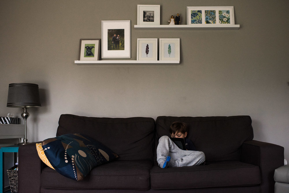 boy plays on his ipad o the couch