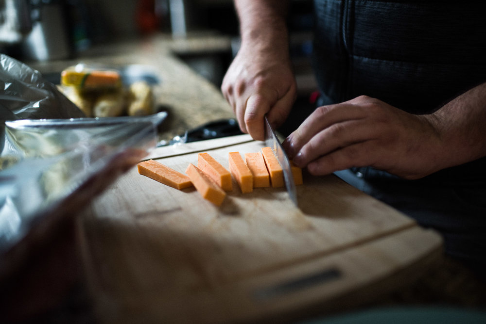male hands cutting cheese in natural light