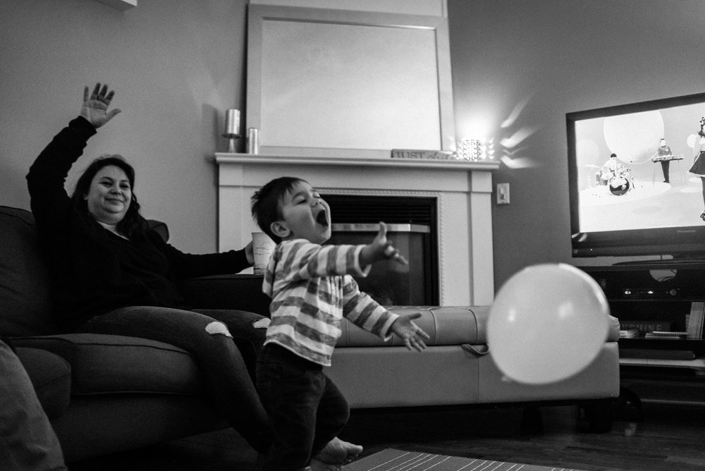 toddler in stripy shirt plays with balloon while mom looks on