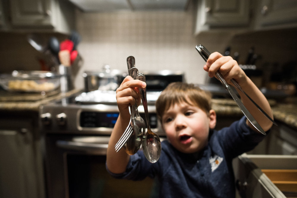 boy holds up handfuls of cutlery
