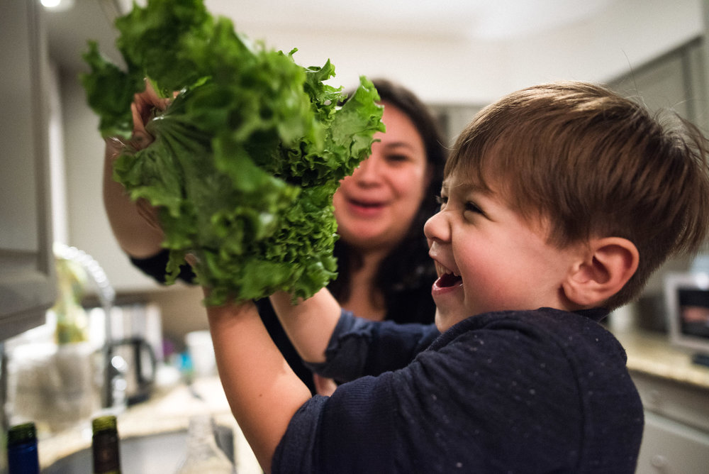 boy and mum laugh over green lettuce
