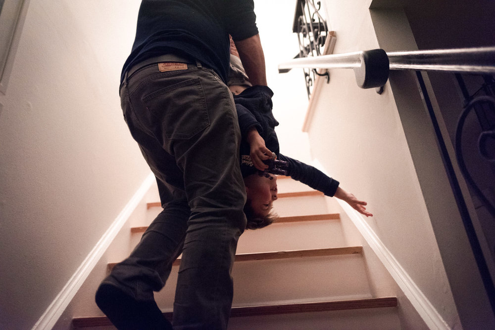 dad carries boy upside down upstairs
