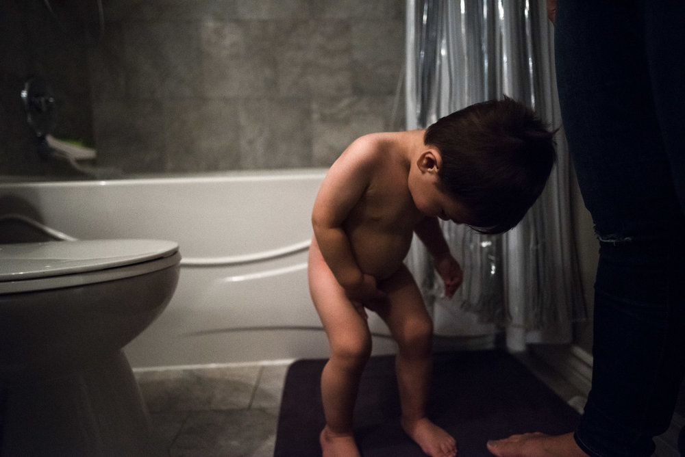 boy looks down in front of bathtub