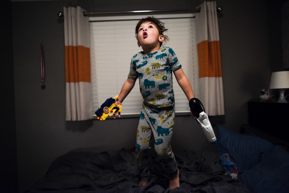 boy in PJs jumps on the bed with toy guns