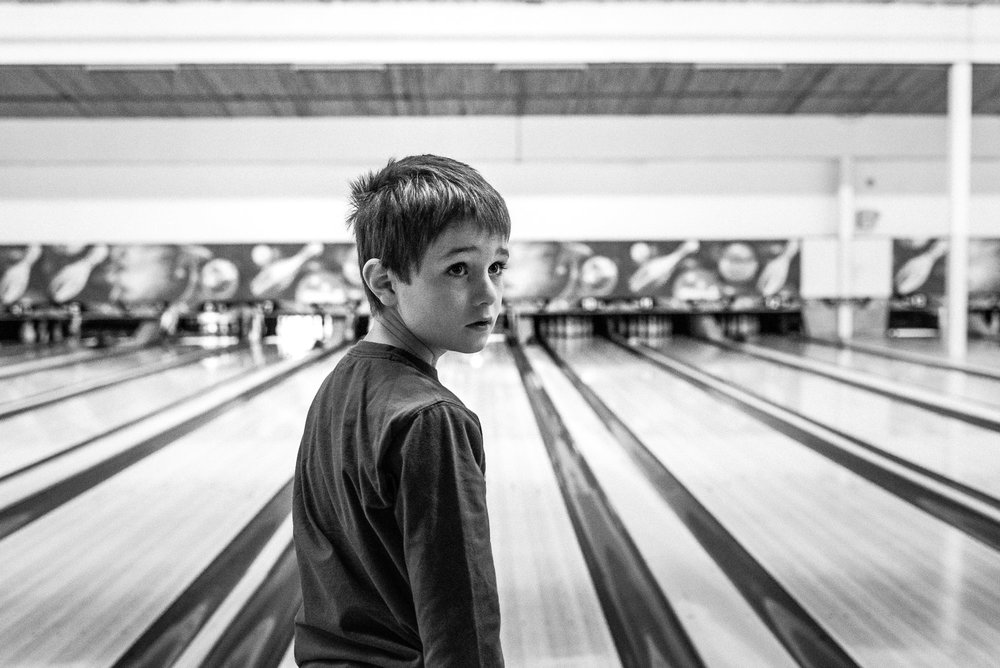 black and white photograph of boy looking back from a bowling alley
