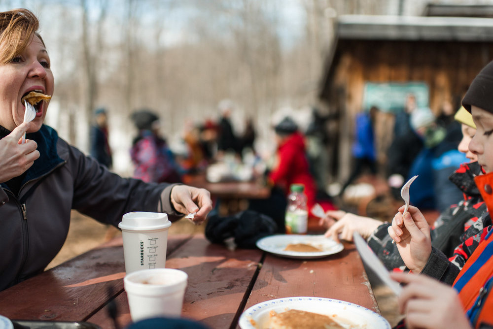 mother and children eat pancakes outdoors