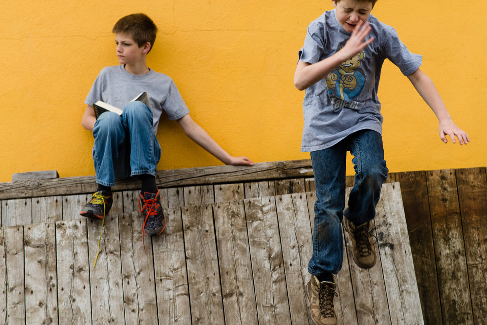 boy jumps from a wooden crate as his brother sits and reads