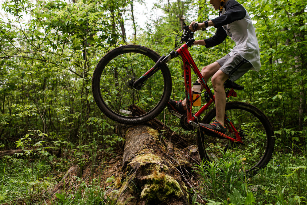 boy jumps over log on a mountain bike in a green forest